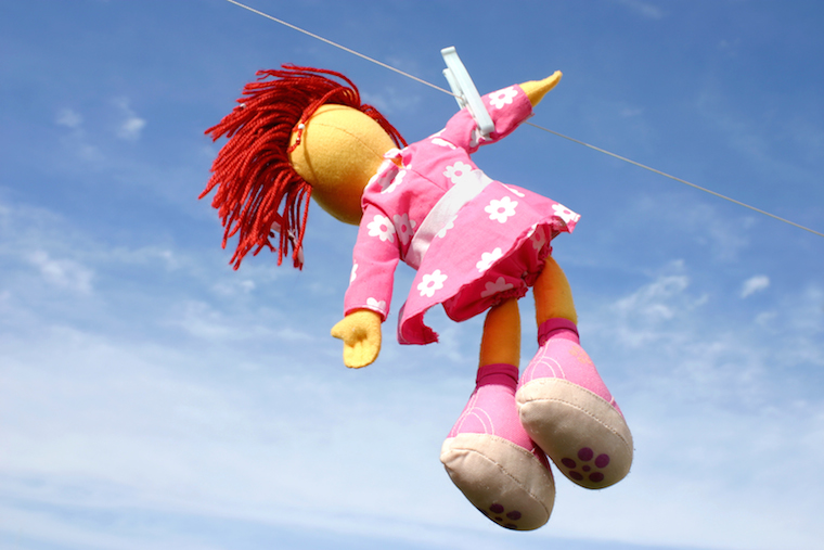 Colorful doll hanging on the laundry wire against blue sky and drying